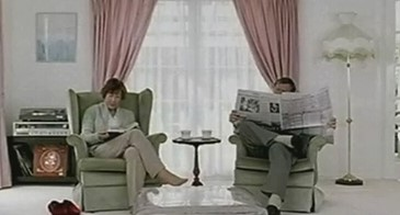 couple sitting in a clean white living-room, reading